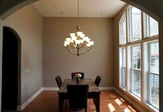 Formal dining room with a cathedral ceiling, large windows and a chandelier.