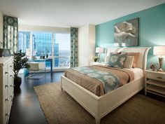 Applying aqua to just an accent wall sets a playful tone in this bedroom. The color is grounded by layers of neutrals on the bed, floor and furnishings.