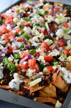 Greek Gyro Pita Nachos _ Top with Tzatziki Sauce, diced tomatoes, lettuce, cucumbers, olives, red onion and remaining feta cheese.