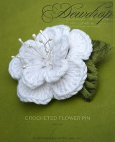 Dewdrop Crocheted Flower Pin. Free Pattern for Kids and Adult- Walk in summer woods any time of the year with the Dewdrop Pin! This free pattern features double layers of crochet petals framing a shower of stamens, trimmed with satin leaves in refreshing green. Wear it pinned to your clothes or in your hair.  This PDF pattern is available for download for FREE . . .