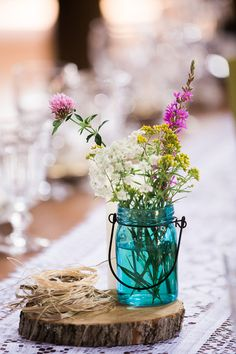 Colorful rustic chic wedding centerpiece idea - teal blue mason jars filled with colorful fresh flowers {Lovebird Studio}