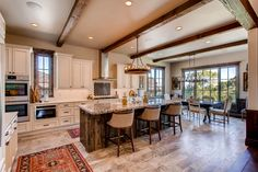 Rustic open concept kitchen with white cabinets and granite counter tops