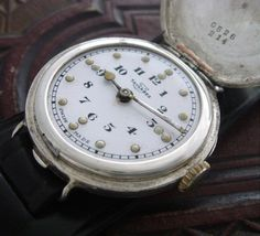 Third view of the World War I Braille watch.  Another possibility is that this was meant to be used at night in the trenches, since the dots seem to be luminous (radium, considered at the time to be harmless and even beneficial).  On the other hand, any similar watch could be opened to feel the hands; you don't need the dots.  The minute hand seems to have been replaced with a sturdier one.