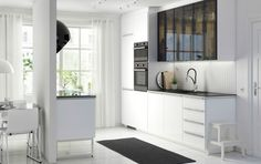 Modern white kitchen with METHOD Ringhult fronts in high gloss white, HÄLLESTAD black countertops and Jutis glass doors in smoked glass