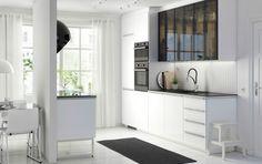 Una moderna cocina METOD blanca con frontales RINGHULT en blanco brillante, encimeras HÄLLESTAD negras y puertas de cristal ahumado JUTIS