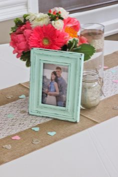 Coral + Mint Wedding centerpiece. Painted frame, floral centerpiece in mason jar, candles in glass vases, burlap table runner with lace and confetti hearts // Celebration Flair