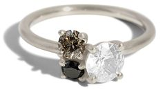 This ring features a white sapphire in a custom basket setting clustered with a champagne diamond and black diamond. Shown in 14kt white gold in a satin finish.