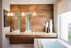 Il parete rivestito in legno aggiunge calore naturale al bagno