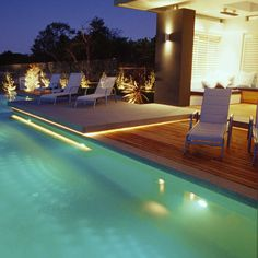Evening lighting around a pool and sitting area.