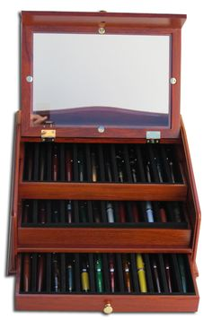 Girologio Italian Rosewood 36 Pen Display Chest. From the noted Italian company Giro Logio comes this hand-crafted solid rosewood thirty-six pen holder and display chest. Each tray is independently removable and holds twelve pens. Two trays can be seen through the glass cover, while the third is in the lower-tier drawer. Many different pen sizes will fit comfortably into each slot. This is the perfect solution for protecting and showcasing your most valued fountain pens. Our price $240.