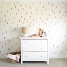 Paint brush wall decals placed in a pattern on a beige wall behind a white dresser. Each wall decal features a different shade of pink, orange, corals, etc.