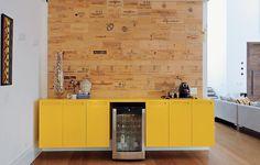 """O amarelo rouba todas as atenções da adega, instalada em uma das divisórias do bufê. """"A cor foge do estilo da minha casa, mas escolhi para disfarçar"""", diz a arquiteta Luita Trench. Na parede, pedaços de madeira levam a impressão de rótulos de vinhos"""