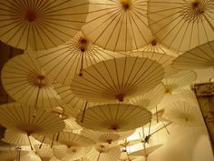 Across the Ceiling  White paper parasols with halogen lights  By Samuel Wood