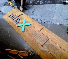 Rótulo de madera con el logotipo en relieve, cortado a mano también en madera.