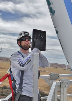 A wind technician takes pictures of blade damage with a Sequoia CMMS Tablet Application. Pictures and comments will be in a report in the owners hands soon after the technician gets down tower. Photo: Performance Composites