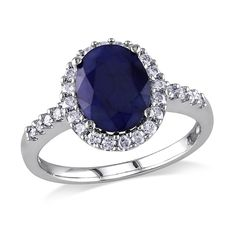 The sparkling elegance of this Sapphire and Diamond Halo Engagement Ring will last a lifetime. Crafted in lustrous white gold, this ring features an oval-cut (10mm x 8mm) sapphire gemstone in the center and 28 round-cut, buttercup-set diamonds (G-H, I1-I2) shimmering along the band.