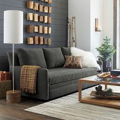 Combination of brown and grey, white fluffy pillow, brown wooden floor, floor light next to the couch.