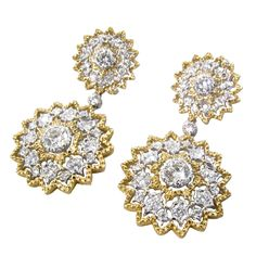 A pair of Buccellati diamond, 18 karat white and yellow gold earrings. Circa 1990. Signed Buccellati Italy and stamped 750. The earrings are designed in a stylized cluster setting, with a larger detachable cluster with bezel set diamond below. The 2 diamonds in the center of the tops weigh a total of approximately .40 carat; and the two diamonds in the center of the drops total approximately 1.40 carats. The earrings contain a total of 54 diamonds weighing a total of approximately 3.75…