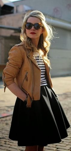 Light brown leather jacket black skirt with lined black and white sweater.