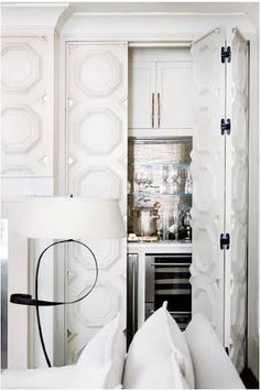 White with White. Panel mouldings dress up white bi-fold doors. Great idea as to how to cover the clutter of a built-in bar.