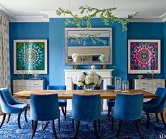 A blue dining room displaying two Damien Hirst Butterfly artworks   archdigest.com: