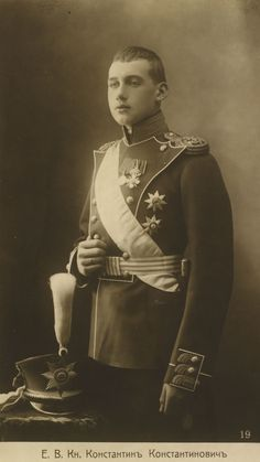 Príncipe Constantino Constantinovich em cerca de 1907. Ele está virado, em parte, para a esquerda e está vestindo uniforme militar com uma faixa e insígnia. Há um chapéu com uma pluma de penas de altura em uma mesa ao lado dele para a esquerda.