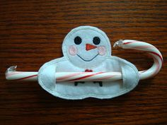 Felt snowman holding candy cane.