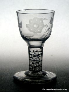 """An Opaque Twist Firing Glass c1760. It has an Ogee bowl engraved with a carnation a simple metaphor for """"coronation"""". Also a very rare example of another plant with its flower head being symbolically cut. Double Series Opaque Twist Stem with a pair of spiral threads and a spiral gauze. Sits on a thick firing foot with a snapped pontil. http://scottishantiques.com/white-sorrel?filter_name=firing#.VjZvgsbX5TM"""