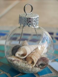 - Make your own stunning nautical beach inspired Christmas ornaments by filling glass ornament balls with sand, tiny seashells, beach glass, raffia, tiny stones and nautical-inspired rope! Would be good to remember beach trips. Beach Christmas Ornaments, Nautical Christmas, Noel Christmas, Christmas Projects, Glass Ornaments, Holiday Crafts, Christmas Bulbs, Christmas Decorations, Seashell Ornaments