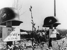 Wooden crosses, topped with the helmets of fallen German soldiers, are seen on May 17, 1940, at an unknown location somewhere along the Norwegian frontline, during the German invasion of the Scandinavian country. The signs have the name and date of death of the men written on it.
