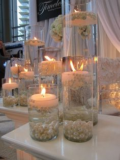 Glass cylinders filled with water and floating candles and pearls. by helene