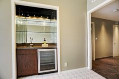 Convenient Wet Bar with wine and beverage refrigerator. Granite counter top, bar sink/faucet, glass shelving. storage cabinet as well.