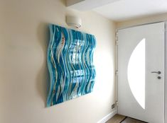This bespoke glass wall art is from a home in Hertford, Hertfordshire. Three sculpted wave panels go together to create a stunning glass wall art installation. They display a classic wave design that complements the shape of the glass itself, rising and falling away from the wall with a mixture of vibrant blue shades and warmer off-white hues. Some extra colour has been sprinkled in for good measure!
