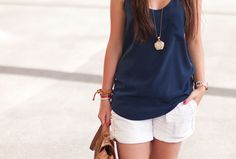 navy blue tank top, gold charm necklace, white shorts, and structured tan satchel bag