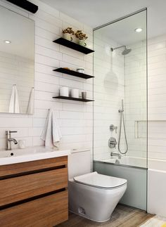 Sleek, dark floating shelves in the all-white contemporary bathroom hold their own - Decoist