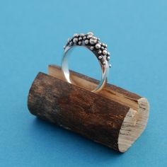 Ring | Lucie Veilleux. Sterling silver. block of wood with saw bands across