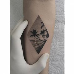 Fine line style beach rhombus tattoo on the inner forearm.