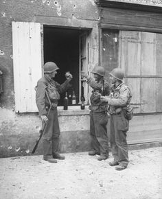 Normandy Invasion On the second day of the Normandy invasion during WWII, American GIs toasting each other w. wine at open window after locating German sniper during advance into Ste. Mere-Eglise. Normandy, France, June 7, 1944
