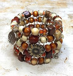 Rustic, Earthy, Alluring.... This chunky bracelet radiates your inner bohemian style. No need to get several stacking my bracelets when you can purchase just one bracelet that satisfy your needs. This tribal bracelet is crafted using stainless steel memory wire, brown artisan beads, wood and coconut wood beads, orange turquoise beads. picture jasper beads, red coral beads, antique bronze button bead, silvertone metal spacer beads and tree of life charms. This hippie bracelet fits an average…