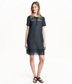 Black. Short, straight-cut dress in woven cotton-blend fabric with hemstitch details. Concealed button placket, short sleeves, side pockets, and lace at hem
