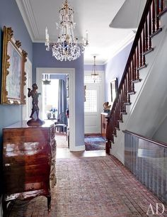 A traditional New York entry hall featuring a large Swedish cut-glass chandelier and an Italian parquetry commode, both 18th century   archdigest.com