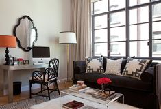 This room features a great mix of textures accented with a bit of pattern-- the diamond pattern on the rug, the trim on the pillows, the flokati rug-- everything works so well together.