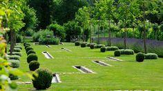 Water channel through parted grass. Les jardins du Chaigne, France