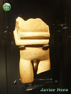 """La colocación de brazos es típica de las figuras femeninas de tipo canónico. Una característica inusual es que los antebrazos no se tocan. Los genitales están tallados en redondo de forma naturalista. De la variedad Spedos del tipo canónico, la figura es una representación única de la figura masculina en dimensiones monumentales. Atribuido al """"Maestro Goulandris"""". Periodo EC II, fase Syros (2800-2300 a. C.) Museo del Arte Cicládico, Atenas."""