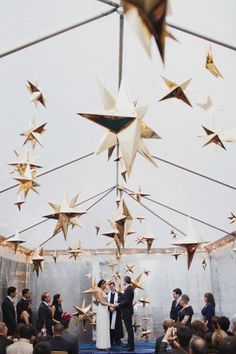 Celestial-themed wedding ceremony decor idea - hanging gold stars {Les Loups]
