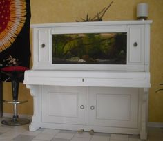 A beautiful fish aquarium by repurposing an old upright piano!  They even utilized the space underneath by putting caninet doors on it!