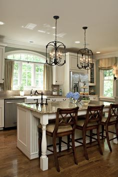 Traditional kitchen with painted white cabinets, a large kitchen island with room for 3 barstools, built in bench for the breakfast nook and desk with cork bulletin board - www.insterior.com
