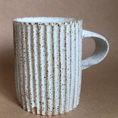 Hand formed and carved of stoneware clay with a speckled matte white glaze.   Each mug is slightly different due to their one of a kind nature. 4 1/4   inches tall, 3 1/4 inches diameter, holds 12 ounces. Made by hand in Los   Angeles California.
