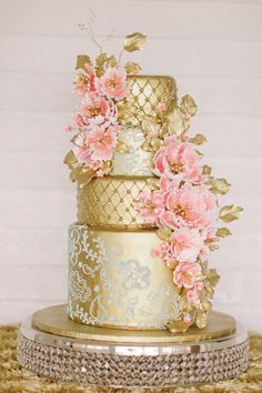 the most amazing gold wedding cake with pink flower accents