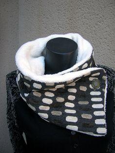 Grand col en tissu doublé de polaire et boutonné sur le côté.